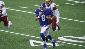 New York Giants' Daniel Jones (8) runs away from Washington Football Team's Landon Collins (26) during the first half of an NFL football game Sunday, Oct. 18, 2020, in East Rutherford, N.J. (AP Photo/John Minchillo)