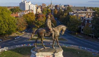 The afternoon sun illuminates the statue of Confederate General Robert E. Lee on Monument Ave in Richmond, Va., Monday, Oct. 19, 2020. A Richmond judge heard arguments in a lawsuit over the Governors' order to remove the statue. (AP Photo/Steve Helber)