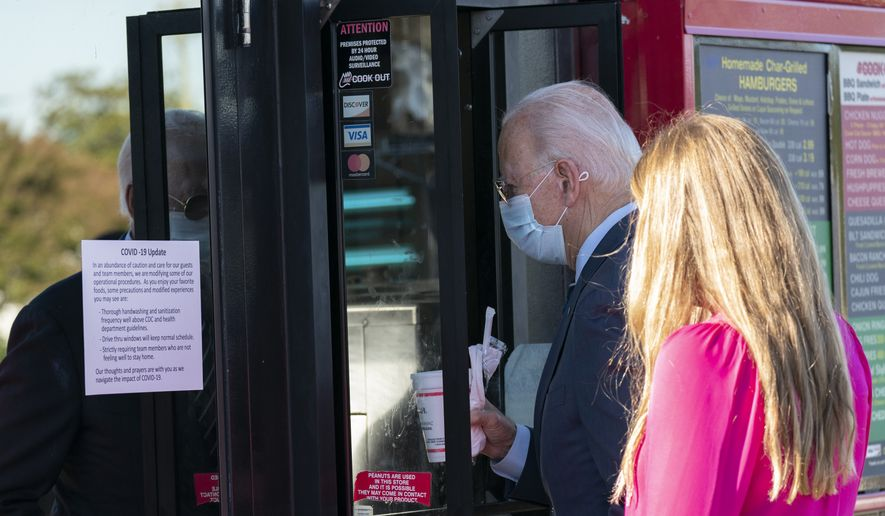 Democratic presidential candidate former Vice President Joe Biden and his granddaughter Finnegan order at window of Cook Out in Durham, N.C., Sunday, Oct. 18, 2020. (AP Photo/Carolyn Kaster)