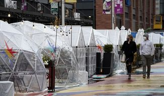 People walk by outdoor plastic dining bubbles on Fulton Market in Chicago, Sunday, Oct. 18, 2020. Colder temperatures are providing a new challenge for restaurants during the coronavirus pandemic, but there's a solution being developed in Fulton Market. (AP Photo/Nam Y. Huh)
