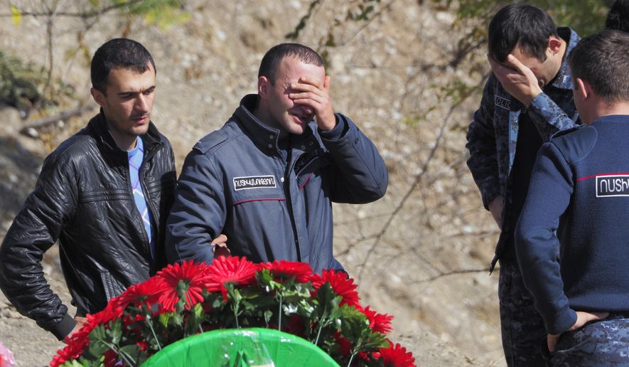 People grieve at the graveside of their relative and friend killed during a military conflict, at a cemetery in Stepanakert, the separatist region of Nagorno-Karabakh, Sunday, Oct. 18, 2020. Armenia and Azerbaijan are trading accusations of violating the new cease-fire in their conflict over the separatist Nagorno-Karabakh territory despite a true announced Saturday that was supposed to take effect at midnight. It is a second attempt to establish a cease-fire in the region since heavy fighting there broke out on Sept. 27. (AP Photo)