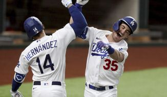 Los Angeles Dodgers' Cody Bellinger, right, celebrates his solo home run with Enrique Hernandez against Atlanta Braves relief pitcher Chris Martin during the seventh inning in Game 7 of a baseball National League Championship Series, Sunday, Oct. 18, 2020, in Arlington, Texas. (Curtis Compton/Atlanta Journal-Constitution via AP)