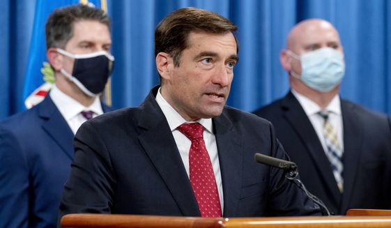 Assistant Attorney General for the National Security Division John Demers, center, accompanied by FBI Deputy Director David Bowdich, left, and FBI Special Agent in Charge of the Pittsburgh field office Michael Christman, right, speaks at a news conference at the Department of Justice, Monday, Oct. 19, 2020, in Washington. (AP Photo/Andrew Harnik, pool)