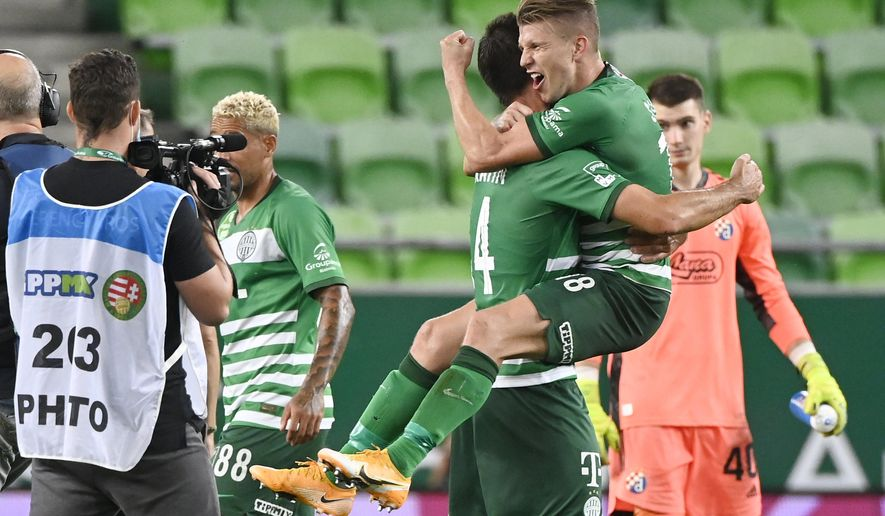 FILE - In this Wednesday, Sept. 16, 2020 file photo, David Siger, right, and Ihor Kharatin of Ferencvaros celebrate their win against Dinamo Zagreb after their Champions' League qualifying third round soccer match in Groupama Arena in Budapest, Hungary. Hungarian champions Ferencvaros return this week to European soccer's biggest stage after a 25-year gap looking to revive a proud history. Ferencvaros beat Juventus in a European final in the 1960s and its star player then won the Ballon d'Or as the continent's best. (Szilard Koszticsak/MTI via AP, file)