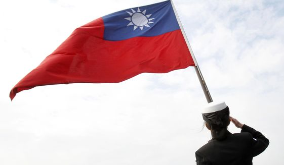In this Jan. 31, 2018, file photo, a Taiwanese military officer salutes to Taiwan's flag onboard Navy's 124th fleet Lafayette frigate during military exercises off Kaohsiung, southern of Taiwan.   (AP Photo/Chiang Ying-ying, File)  **FILE**