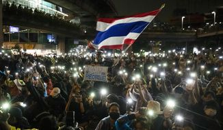 Pro-democracy protesters wave the Thailand national flag as others shine their mobile phone lights during an anti-government protest in Bangkok, Thailand, Sunday, Oct. 18, 2020. Thai police on Sunday declined to say whether they were taking a softer approach toward student anti-government demonstrations, after several mass rallies attracting thousands of protesters ended peacefully in Bangkok on Saturday. (AP Photo/Sakchai Lalit)