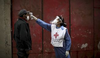 FILE - In this June 6, 2020 file photo, a Red Cross volunteer measures the temperature of man inside the Fraga slum, during a government-ordered lockdown to curb the spread of the new coronavirus, in Buenos Aires, Argentina. Argentina reached 1 million confirmed coronavirus cases on Monday, Oct. 19, 2020, according to the Ministry of Health. (AP Photo/Natacha Pisarenko, File)