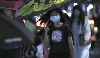 People wear face masks to protect against the spread of the coronavirus in Taipei, Taiwan, Saturday, Oct. 17, 2020. (AP Photo/Chiang Ying-ying)