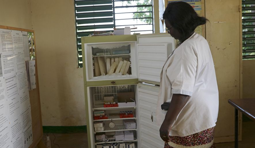 Marguerite Ouangraoua, a nurse at the health clinic in Zeguedessin village on the outskirts of Burkina Faso's capital, Ouagadougou, opens the fridge where the clinic keeps the vaccines, Thursday Oct. 8, 2020. The vaccine cold chain hurdle is just the latest disparity of the pandemic weighted against the poor, who more often live and work in crowded conditions that allow the virus to spread, have little access to medical oxygen vital to COVID-19 treatment, and whose health systems lack labs, supplies or technicians to carry out large-scale testing. (AP Photo/Sam Mednick)