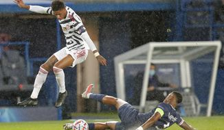 Manchester United's Marcus Rashford leaps over a challenge by PSG's Presnel Kimpembe during the Champions League group H soccer match between Paris Saint-Germain and Manchester United at the Parc des Princes in Paris, France, Tuesday, Oct. 20, 2020. (AP Photo/Michel Euler)