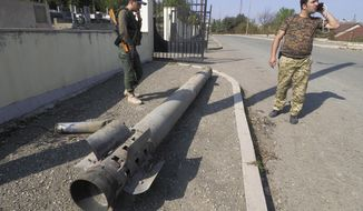 People stand near a tail of a multiple rocket 'Smerch' after shelling by Azerbaijan's artillery in Stepanakert, in the separatist region of Nagorno-Karabakh, Tuesday, Oct. 20, 2020. Armenia and Azerbaijan reported more fighting on Tuesday over the separatist territory of Nagorno-Karabakh, where clashes have continued for over three weeks despite two attempts at establishing a cease-fire. (AP Photo)