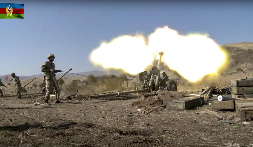 In this image taken from video released by Azerbaijan's Defense Ministry on Tuesday, Oct. 20, 2020, Azerbaijan army soldiers fire an artillery piece during fighting with forces of the self-proclaimed Republic of Nagorno-Karabakh. Azerbaijan Defense Ministry claims that Armenian forces tried to carry out an offensive that was met by an artillery strike from Azerbaijan, causing a large number of casualties among Armenian forces. (Azerbaijan's Defense Ministry via AP)