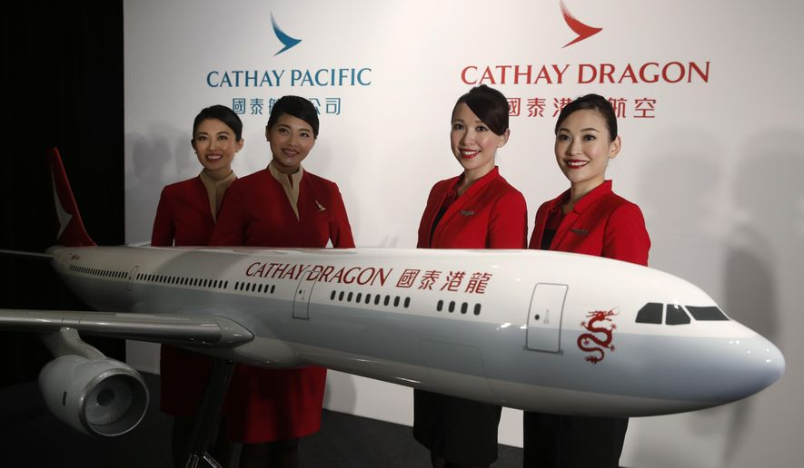 FILE - In this Jan. 28, 2016, file photo, flight attendants pose next to a model jet of Hong Kong airline Cathay Dragon, formerly known as Dragonair in Hong Kong. Hong Kong airline Cathay Pacific Airways on Wednesday, Oct. 21, 2020, said it would cut 8,500 jobs and shut down its regional airline unit in a corporate restructuring, as it grapples with the plunge in air travel due to the pandemic. The company will also shut down Cathay Dragon, its regional airline unit, with operations ceasing from Wednesday. (AP Photo/Kin Cheung)
