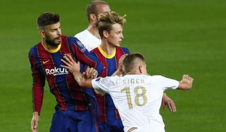 Ferencvaros' David Siger, right, pushes Barcelona's Gerard Pique during the Champions League group G soccer match between FC Barcelona and Ferencvaros at the Camp Nou stadium in Barcelona, Spain, Tuesday, Oct. 20, 2020. (AP Photo/Joan Monfort)
