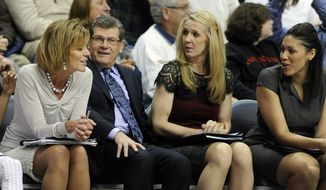 FILE - In this Feb. 4, 2014, file photo, Connecticut head coach Geno Auriemma shares a light moment with his bench with associate head basketball coach Chris Dailey, left, and assistant coaches Shea Ralph, second from right, and Marisa Moseley during the second half of UConn's 102-41 victory over SMU in an NCAA college basketball game in Storrs, Conn. The University of Connecticut has agreed to pay a total of just under $250,000 to seven women, including four members of Geno Auriemma's 2014 women's basketball coaching staff, after the U.S. Labor Department found they had been underpaid when compared with men in similar positions.  (AP Photo/Fred Beckham, File)