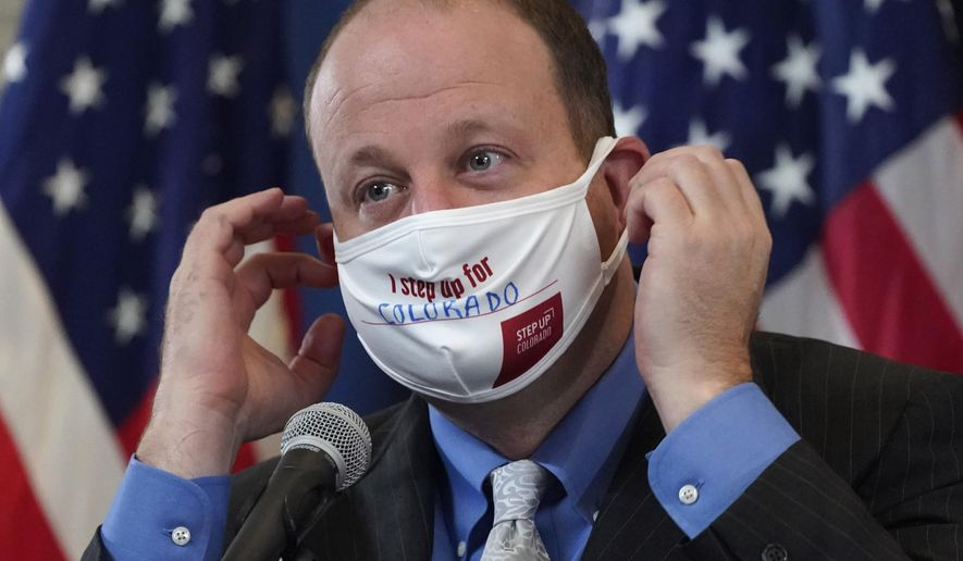 Colorado Governor Jared Polis adjusts his face covering bearing the state's new message to encourage residents to protect against COVID-19 during a news conference about the steady increase in cases of the new coronavirus in the state Tuesday, Oct. 20, 2020, in Denver. (AP Photo/David Zalubowski)