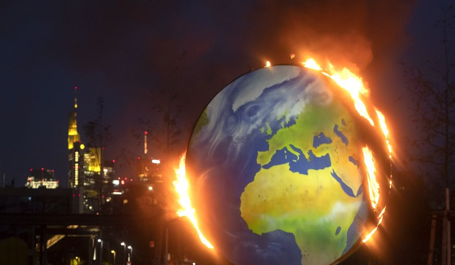 "A makeshift globe burns in front of the European Central Bank in Frankfurt, Germany, Wednesday, Oct. 21, 2020. Activists of the so-called ""KoalaKollektiv"", an organization asking for climate justice, protested with the burning of the globe against the ECB's climate policy. (AP Photo/Michael Probst)"