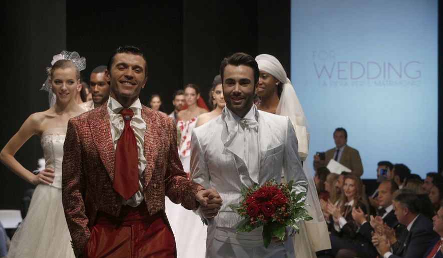 """Models on the catwalk during a wedding fashion show with same-sex couples, dubbed """"The rainbow wedding fashion show,"""" part of a """"wedding fair"""" taking place in Rome, Thursday, Oct. 23, 2014. Pope Francis endorsed same-sex civil unions for the first time as pope while being interviewed for the feature-length documentary Francesco, which premiered Wednesday, Oct. 21 2020, at the Rome Film Festival. (AP Photo/Domenico Stinellis)"""