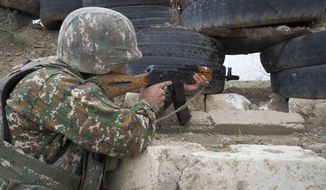 An Ethnic Armenian soldier holds a Kalashnikov machine gun as he looks toward Azerbaijan's positions from a dugout at a fighting position on the front line, during a military conflict against Azerbaijan's armed forces in the separatist region of Nagorno-Karabakh, Wednesday, Oct. 21, 2020. Armenia's prime minister has urged citizens to sign up as military volunteers to help defend the country amid the conflict with Azerbaijan over the disputed territory of Nagorno-Karabakh as intense fighting has raged for a fourth week with no sign of abating. (AP Photo)