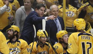 In this May 7, 2017, file photo, then-Nashville Predators coach Peter Laviolette, center left, and associated coach Kevin McCarthy, center right, talk during Game 6 of a second-round NHL hockey playoff series against the St. Louis Blues in Nashville, Tenn. Kevin McCarthy joined Peter Laviolette's Washington Capitals coaching staff as expected Wednesday, Oct. 21, 2020, continuing the pair's partnership that has lasted for more than 15 years. (AP Photo/Mark Humphrey, File)  **FILE**