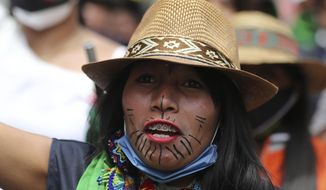 An Indigenous woman marches during a national strike in Bogota, Colombia, Wednesday, Oct. 21, 2020. Workers' unions, university students, human rights defenders, and Indigenous communities have gathered for a day of protest in conjunction with a national strike across Colombia. The protest is against the assassinations of social leaders, in defense of the right to protest and to demand advances in health, income and employment. (AP Photo/Fernando Vergara)