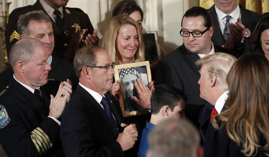 In this Oct. 26, 2017, file photo, Jeanne Moser, center, of East Kingston, N.H., watches as President Donald Trump reaches out to touch a photo of her son, Adam Moser, during an event to declare the opioid crisis a national public health emergency in the East Room of the White House in Washington. Adam was 27 when he died from an apparent fentanyl overdose. The coronavirus outbreak and the Trump administration's response to the pandemic have been a dominating theme in this year's presidential race. That has overshadowed debate over how to handle the nation's drug overdose crisis, which has contributed to the deaths of more than 470,000 Americans over the last two decades. (AP Photo/Pablo Martinez Monsivais, File)