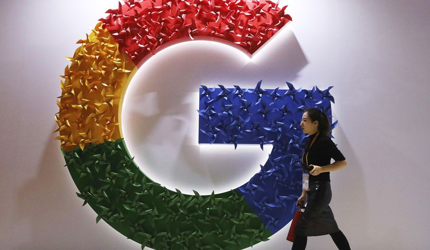 In this Monday, Nov. 5, 2018 file photo, a woman walks past the logo for Google at the China International Import Expo in Shanghai. (AP Photo/Ng Han Guan, File)  **FILE**