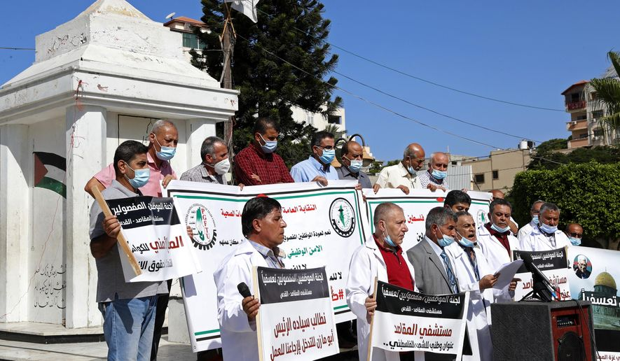 """Medical workers wear face masks and hold placards while staging a sit-in protest at the Unknown Soldier Square in Gaza City, Wednesday, Oct. 21, 2020. Arabic reads: """"Makassed Hospital is a national address for the Palestinian people."""" """"We call on President Abu Mazen to intervene and bring us back to work."""" Seven medical workers from the Gaza Strip said Wednesday an Israeli travel ban deprived them from getting to the east Jerusalem hospital where they worked for many years and the hospital eventually fired them. (AP Photo/Adel Hana)"""