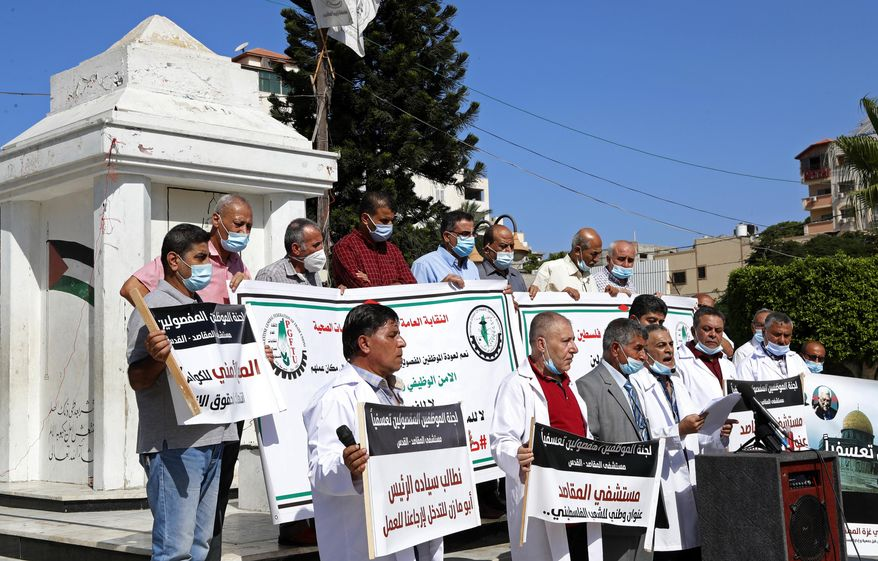 "Medical workers wear face masks and hold placards while staging a sit-in protest at the Unknown Soldier Square in Gaza City, Wednesday, Oct. 21, 2020. Arabic reads: ""Makassed Hospital is a national address for the Palestinian people."" ""We call on President Abu Mazen to intervene and bring us back to work."" Seven medical workers from the Gaza Strip said Wednesday an Israeli travel ban deprived them from getting to the east Jerusalem hospital where they worked for many years and the hospital eventually fired them. (AP Photo/Adel Hana)"
