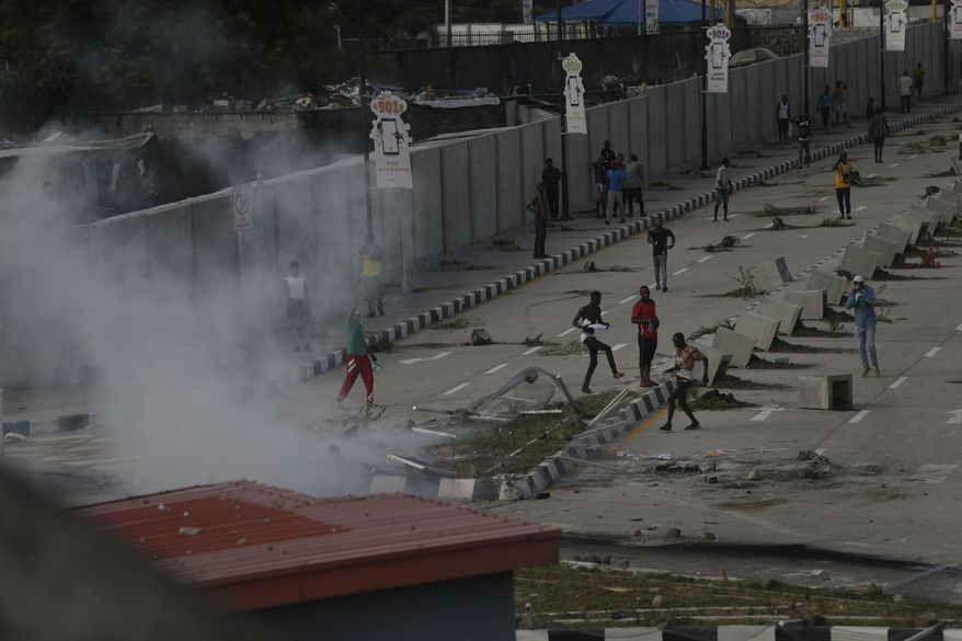 Protesters run away as police officers use teargas to disperse people demonstrating against police brutality in Lagos, Nigeria, Wednesday, Oct. 21, 2020. After 13 days of protests against alleged police brutality, authorities have imposed a 24-hour curfew in Lagos, Nigeria's largest city, as moves are made to stop growing violence. ( AP Photo/Sunday Alamba)