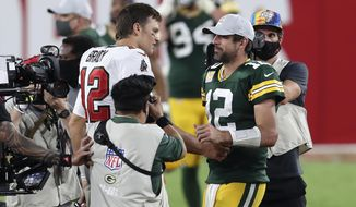 Tampa Bay Buccaneers quarterback Tom Brady, left, shakes hands with Green Bay Packers quarterback Aaron Rodgers after the Bucs defeated the Packers during an NFL football game Sunday, Oct. 18, 2020, in Tampa, Fla. (AP Photo/Mark LoMoglio)