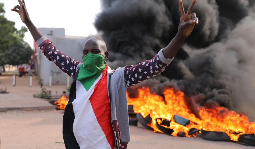 A demonstrators gives the victory sign at a protest, in Khartoum, Sudan, Wednesday, Oct. 21, 2020. Protesters have taken to the streets in the capital and across the country over dire living conditions and a deadly crackdown on demonstrators in the east earlier this month. Sudan is currently ruled by a joint civilian-military government, following the popular uprising that toppled longtime autocrat Omar al-Bashir last year. (AP Photo/Marwan Ali)