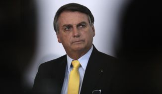Brazil's President Jair Bolsonaro listens during a presentation at the Planalto Presidential Palace in Brasilia, Brazil, Monday, Oct. 19, 2020. The Brazilian government announced the results of clinical tests with use of the drug Nitazoxanide for COVID-19 treatment. (AP Photo/Eraldo Peres)