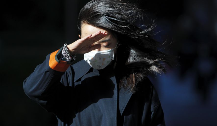 A woman wearing a face mask to help curb the spread of the coronavirus uses her hand to shield from the wind on a street in Beijing, Wednesday, Oct. 21, 2020. (AP Photo/Andy Wong)