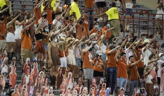 """In this Saturday, Sept. 12, 2020, file photo, fans join in singing """"The Eyes of Texas"""" after Texas defeated UTEP 59-3 in an NCAA college football game in Austin, Texas. Texas athletic director Chris Del Conte said Wednesday, Oct. 14, 2020, he expects players to """"stand together as a unified group"""" to show appreciation for the school and fans during the playing of the school song """"The Eyes of Texas"""" after games, but didn't say what will happen if they refuse. The song has exploded into a thorny controversy after several football players and other athletes said over the summer they no longer wanted to sing it because of its uncomfortable connections to racist elements of the school's past. (AP Photo/Chuck Burton, File)  **FILE**"""