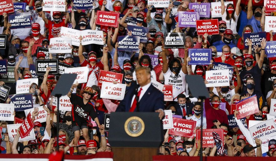 Supporters wave signs as President Donald Trump speaks at a campaign rally in Gastonia, N.C., Wednesday, Oct. 21, 2020. (AP Photo/Nell Redmond)