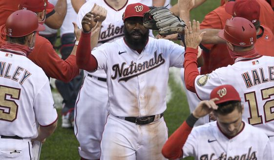 FILE  - In this Sept. 26, 2020, file photo, Washington Nationals' Josh Harrison, center, celebrates after the first baseball game of a doubleheader against the New York Mets, in Washington. The Nationals agreed to terms on a one-year contract Thursday, Oct. 22, with utility man Josh Harrison. (AP Photo/Nick Wass, File)