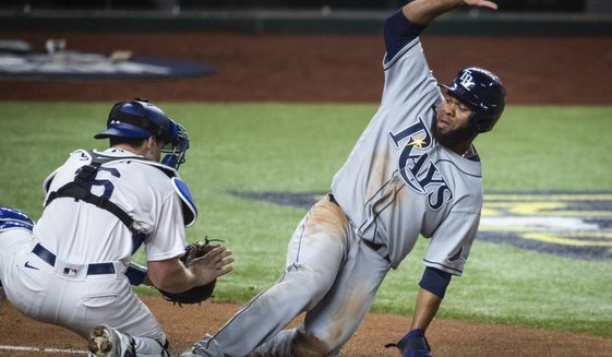 Tampa Bay Rays' Manuel Margot slides as Los Angeles Dodgers catcher Will Smith (16) tags him out at home plate during Game 2 of the baseball World Series, Wednesday, Oct. 21, 2020, in Arlington, Texas. (Yffy Yossifor/Star-Telegram via AP)