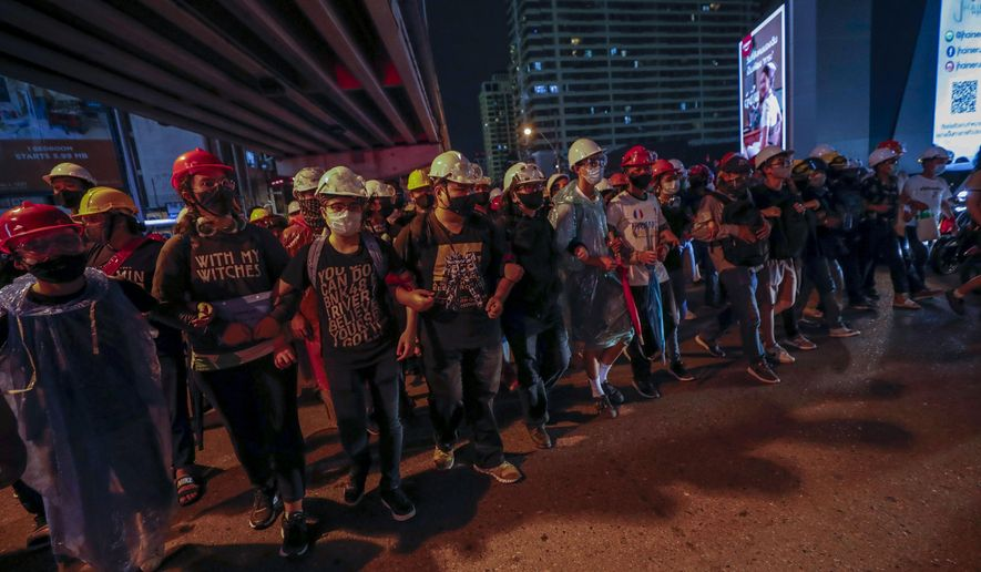 Pro-democracy activists create a human chain to confront a police barricades during their march to the Government House, prime minister's office during a protest march in Bangkok, Thailand, Wednesday, Oct. 21, 2020. Thailand's prime minister on Wednesday pleaded with his countrymen to resolve their political differences through Parliament, as student-led protests seeking to bring his government down continued for an eighth straight day. (AP Photo/Sakchai Lalit)