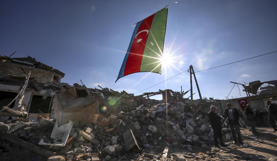 Azerbaijan's national flag flies over destroyed houses in a residential area that was hit by rocket fire overnight by Armenian forces, on Thursday, Oct. 22, 2020 in Ganja, Azerbaijan's second largest city, near the border with Armenia. Heavy fighting over Nagorno-Karabakh is continuing with Armenia and Azerbaijan trading blame for new attacks. The nearly four weeks of hostilities have raised the threat of Turkey and Russia being drawn into the conflict. (AP Photo/Aziz Karimov)