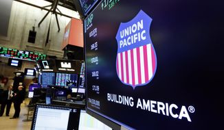 In this Sept. 13, 2019, file photo the logo for Union Pacific appears above a trading post on the floor of the New York Stock Exchange.  On Nov. 17, 2020, the company announced it would give a $1,000 bonus to its employees next month in gratitude for their hard work during the COVID pandemic. (AP Photo/Richard Drew, File)  **FILE**