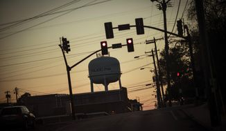 A water tower is framed by electrical wires and traffic lights at sunset in Philadelphia, Miss., Monday, Oct. 5, 2020. (AP Photo/Wong Maye-E)