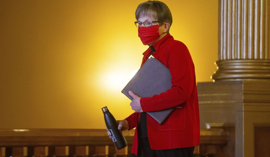 FILE - In this Oct. 13, 2020, file photo, Kansas Gov. Laura Kelly walks toward a news conference at the Statehouse in Topeka, Kan. Kansas' coronavirus positivity rate has climbed above 20%, even as one top GOP lawmaker pushed back against Democratic Gov. Kelly's call for a statewide mask mandate to curb the spread of COVID-19. (Evert Nelson/The Topeka Capital-Journal via AP, File)-