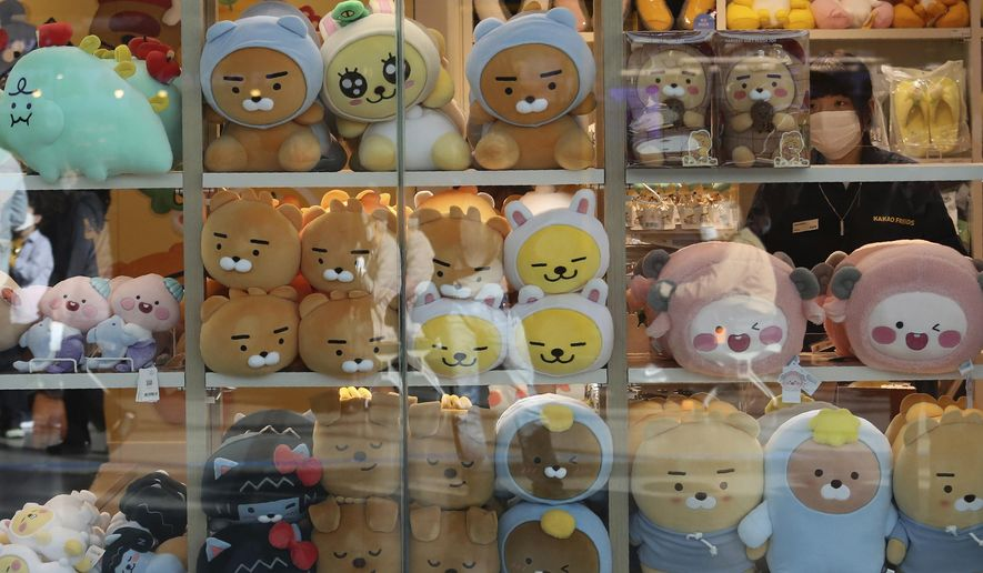 An employee wearing a face mask to help protect against the spread of the coronavirus arranges dolls at a shop in Seoul, South Korea, Thursday, Oct. 22, 2020. The steady spread of the coronavirus caused concern in a country that eased its social distancing restrictions just last week to cope with a weak economy. (AP Photo/Ahn Young-joon)