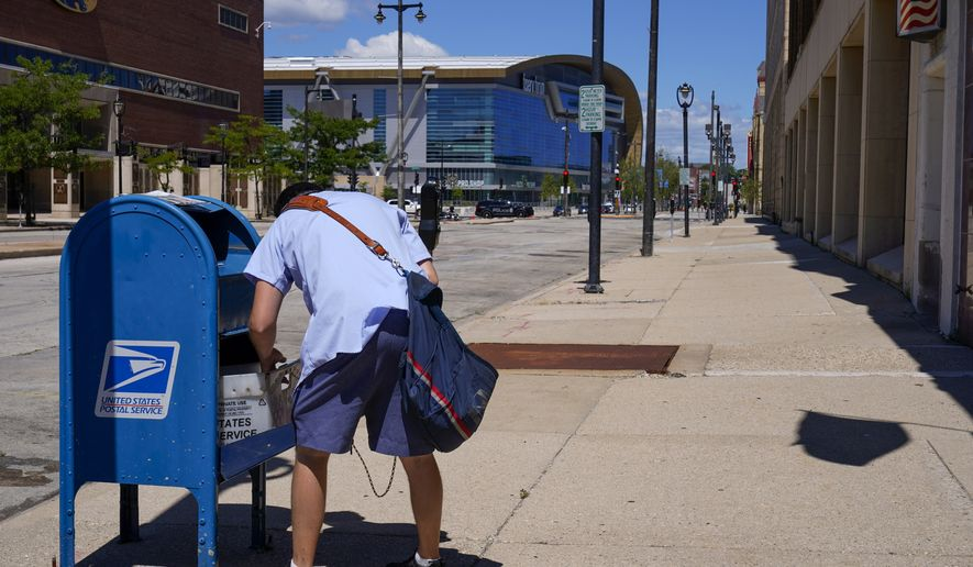 In this Aug. 18, 2020, file photo, a postal worker empties a box near the Fiserv Forum in Milwaukee. U.S. Postal Service records show delivery delays have persisted across the country as millions of Americans began voting by mail, raising the possibility of ballots being rejected because they arrive too late. Parts of the politically coveted battleground states of Wisconsin, Michigan, Pennsylvania and Ohio fell short of delivery goals by wide margins as the agency struggles to regain its footing after a tumultuous summer. (AP Photo/Morry Gash) **FILE**
