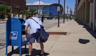 FILE - In this Aug. 18, 2020, file photo, a postal worker empties a box near the Fiserv Forum in Milwaukee. U.S. Postal Service records show delivery delays have persisted across the country as millions of Americans began voting by mail, raising the possibility of ballots being rejected because they arrive too late. Parts of the politically coveted battleground states of Wisconsin, Michigan, Pennsylvania and Ohio fell short of delivery goals by wide margins as the agency struggles to regain its footing after a tumultuous summer. (AP Photo/Morry Gash, File)