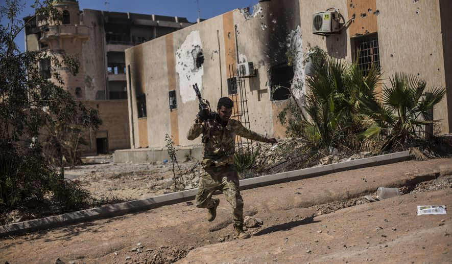 """In this Thursday, Sept. 22, 2016, photo, a fighter of the Libyan forces, affiliated to the Tripoli government, runs for cover while fighting against Islamic State positions in Sirte, Libya, The United Nations said that the two sides in Libyan military talks had reached a """"historic achievement"""" with a permanent cease-fire agreement across the war-torn North African country. (AP Photo/Manu Brabo) **FILE**"""