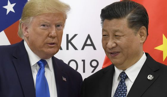 In this June 29, 2019, file photo, U.S. President Donald Trump poses for a photo with Chinese President Xi Jinping during a meeting on the sidelines of the G-20 summit in Osaka, western Japan. Chinese leaders hope Washington will tone down conflicts over trade, technology and security if Joe Biden wins the Nov. 3 presidential election. But any shift is likely to be in style, not substance, as frustration with Beijing increases across the American political spectrum. (AP Photo/Susan Walsh, File)