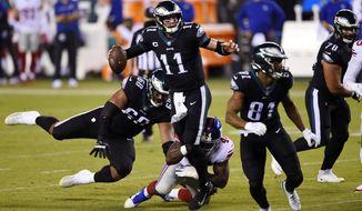 Philadelphia Eagles' Carson Wentz (11) is grabbed by New York Giants' Markus Golden (44) during the first half of an NFL football game, Thursday, Oct. 22, 2020, in Philadelphia. (AP Photo/Derik Hamilton)
