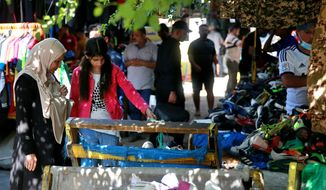 People shop for clothing at the used-clothes market in Baghdad, Iraq, Tuesday, Oct. 20, 2020.  Iraq is in the throes of an unprecedented liquidity crisis, as the cash-strapped state wrestles to pay public sector salaries and import essential goods while oil prices remain dangerously low. (AP Photo/Khalid Mohammed)
